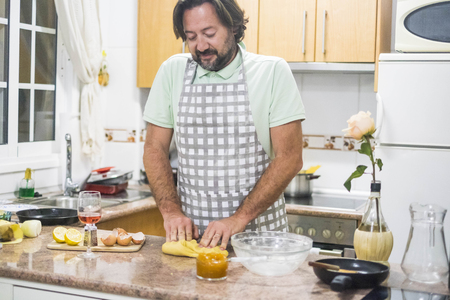 man with beard and apron preparing dough for cake in his home kitchen with glass of wine.