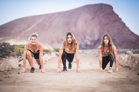 three beautiful runner girls young ready to start and run for hard workout and fitness outdoor activity. build your new and strong body near the beach for a healthy lifestyle concept.. group of people doing sport