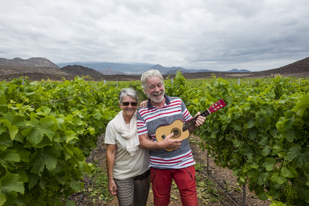 nice beautiful adult couple white hair walk on the fields of wine playing an ukulele guitar. happiness together forever with nice and craziness concept. lifestyle different for retired