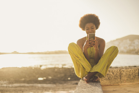 beautiful black race african model with nice hair use the smartphone sit down near the ocean and the beach in freedom leisure vacation activity. contact and connect using wifi with far friends or parents