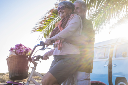 nice beautiful couple of seniors grandfathers going together on a bicycle outdoor in a tropical place. old vintage blue van in the background. happiness elderly concept.