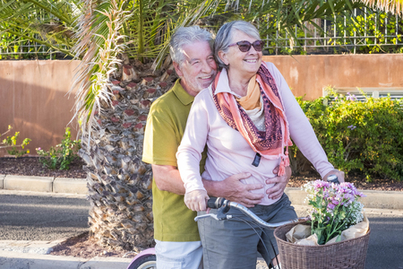 senior couple in love leisure outdoor together on a bike vintage style smiling and having fun under the sun of vacation. alternative way to be retired living in a tropical place