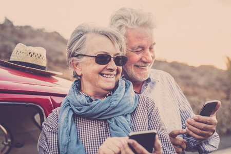 Elderly couple with hat, with glasses, with gray and white hair, with casual shirt, on vintage red car on vacation enjoying time and life. With a cheerful mobile phone smiling immersed in the windy spring weather of the Canary Islands