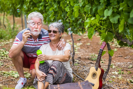 funny and beautiful couple of matures play together with soap bubbles. have fun like children at the age of 70. smiles and laugh with love and tenderness in a vineyard outdoor. spring season and retired concept
