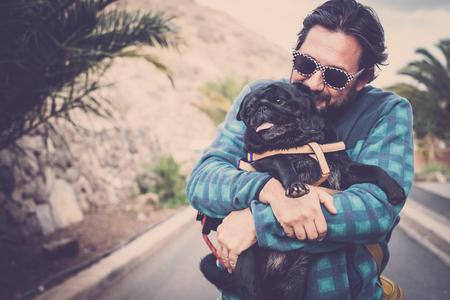 man plays with his black sweet pug puppy dog ??pug 写真素材
