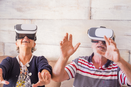 adult couple play and try modern goggled headset at home. hands on hands together with fun and fear. technology for seniors