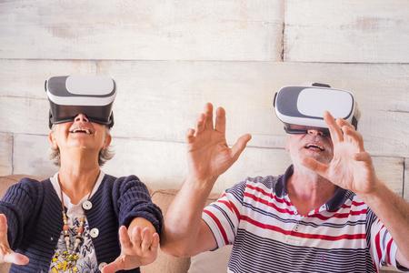 un couple d'adultes joue et essaie un casque à lunettes moderne à la maison. mains sur les mains avec plaisir et peur. technologie pour les seniors