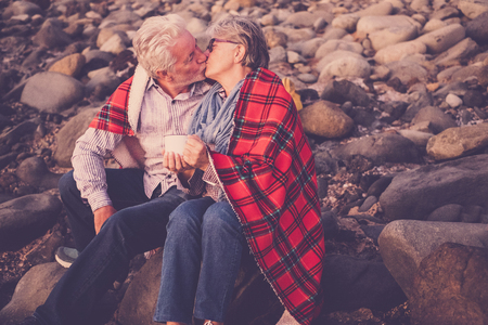 elderly couple and retired man kissing in front of the ocean
