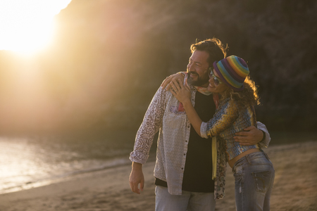 nice caucasian family couple enjoy the leisure time together during the sunset at the beach. vacation and lifetime happy two people concept. golden tones colorsfor outdoor natural scenic place and happy man and woman Stock Photo