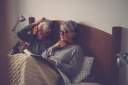caucasian senior adult couple stay and rest on the bed. the wman read a book the man play with goggled headset technology. beautiful model and light from window. Zdjęcie Seryjne