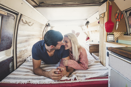 blonde girl and black hair man in love with feeling and passion lay down inside an old vintage restored van for a different lifestyle concept with alternative choice