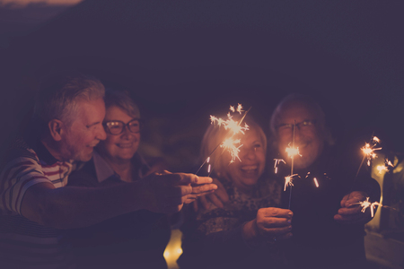 celebration time for party or new year eve for a group of senior friends with fire sparks. averybody together having  fun at night smiling and laughing. Group of four and party concept Imagens