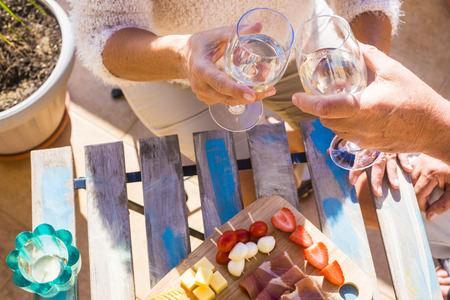 elderly man and woman hands celebrate summer time with snack and drink Imagens