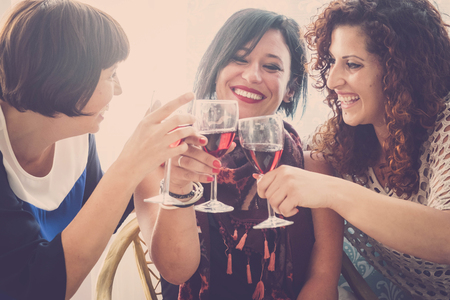 group of people three young women drink some red wine at home to celebrate their friendship. Lot of fun and smilies for a day of party Stock fotó