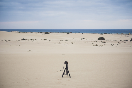 lonely camera with nobody taking pictures in the Corralejo Fuerteventura desert. Ocean view and beautiful sky.