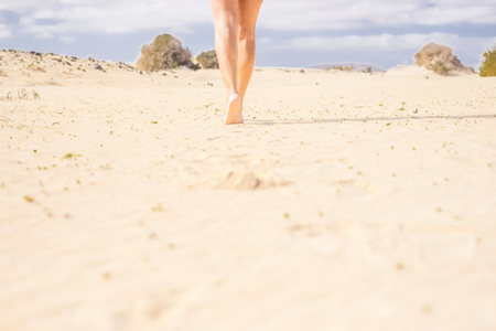 barefoot woman legs walking in the desert of Fuerteventura. Blue horizon and hot yellow ground.