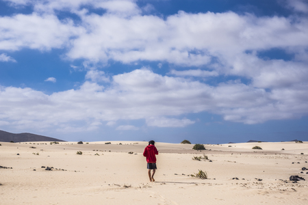 lonely young man with red jacket walking in the niddle of the desert in fuerteventura canary islands spain. nude feet like lost with mountains and nowhere around him. blue sky and yellow sand. Stock Photo