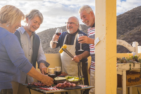 four active senior retired have fun in the terrace at home cooking some bbq everybody smiles and stay together in friendship under a nice sunny day.  vacation and relationship people concept