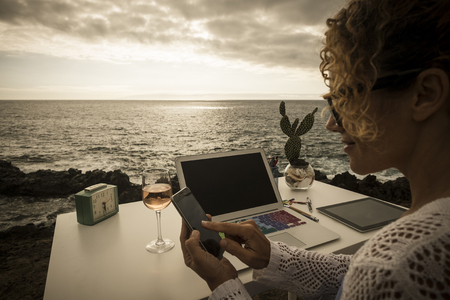 beautiful assistent professional lady at work in alternative freedom concept office in front of the ocean. enjoy a different lifestyle and work with social media like digital nomad Stockfoto
