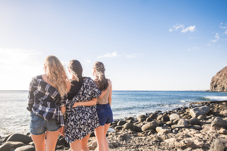 Group of three young nice girls embrace themselves looking at the ocean sunset in vacation. Team moment full of emotions and memories. Sunlight in a blue sky.
