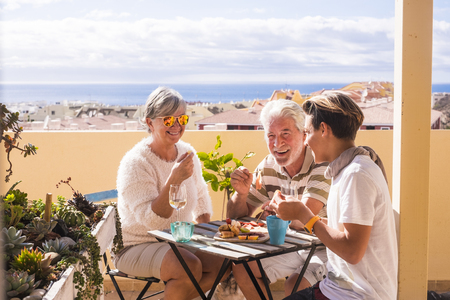 three people different ages eating and enjoying together the rooftop with sea view. Summer lifestyle with amazing panorama. Eat and drink food and beverage. 写真素材