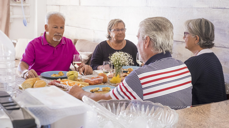 senior adult at home have lunch together in friendship and happiness. all serious speaking about problems and issues. two women and teo men for two families enjoy time in relationship