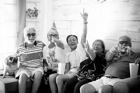 Famille de 4 personnes âgées aux cheveux blancs et un adolescent célèbrent dans le masque en riant et en jouant assis sur le canapé