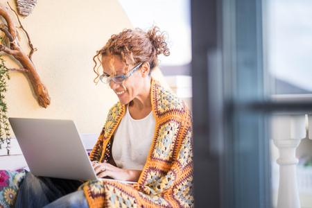 belle femme caucasienne souri travailler avec un ordinateur portable en plein air sur la terrasse. bureau alternatif et style de vie travailler à domicile en toute liberté de l'endroit habituel où les gens travaillent