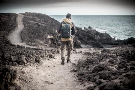 einsamer reisender Mann junges mittleres Alter mit Trekkingkleidung und Rucksack, der auf der Ozeanküste in einer Felsenwüste geht. Folgen Sie einem Pfad mit Meerblick und genießen Sie Freiheit und alternativen Lebensstil