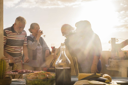 two matures adult couple caucasian people having fun enjoy the dinner time at the sunset on the rooftop terrace outdoor at home. golden tones for leisure men and women activity together celebrating vacation Foto de archivo