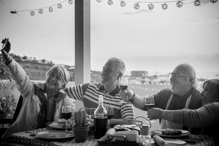 group of aged senior friends adults having dinner and doing party nice time in the rooftop terrace outdoor with wine and food. having fun during the sunset with beautiful sun backlight and amazing view of the ocean and other roofs.