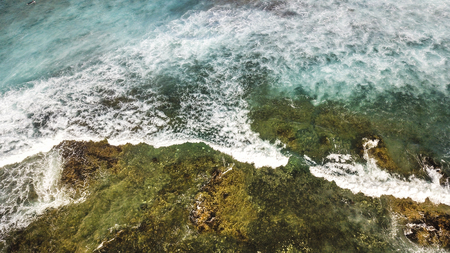 ocean's coast aerial view with blue waves and green natural rocks, vacation and adventure journey concept outdoor