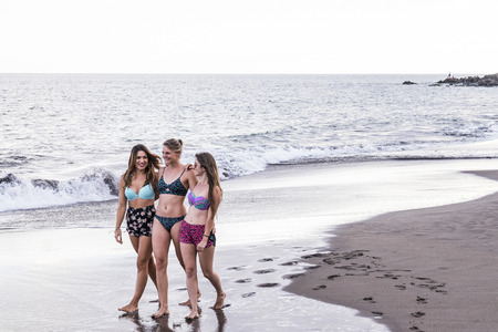 three caucasian cheerful young women walk together hugged on the shore at the beach. summer lifestyle outdoor activity for beautiful girls in vacation. smiling days and happiness