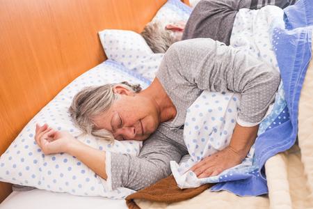 por la mañana, despierta para adultos mayores en casa en la cama. dormir juntos a la luz de la ventana, concepto de vida diurna. Buen descanso para personas caucásicas envejecidas y cansadas. almohada blanca
