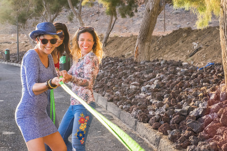 group of females friends with colored and happy clothes casual style enjoy together playing with a cord. happy outdoor leisure activity and smile. enjoy lifestyle and stay young