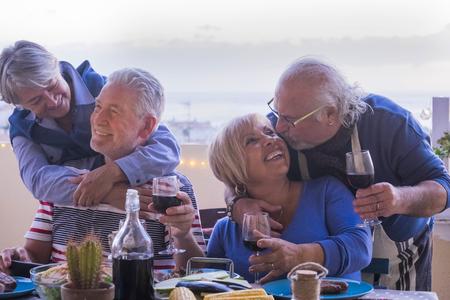 causasian couples mûrs amis s'amusant pendant le dîner ensemble. Embrassez et étreignez et souriez et riez pour un excellent concept de style de vie à la retraite. extérieur sur la terrasse avec vue sur l'océan. vin et nourriture sur la table en été
