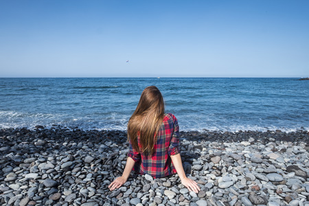 nice girl viewed from rear sit down at the beach and look at the sea. silence and peace feeling in outdoor leisure activity of meditation. enjoy life and see the waves to relax