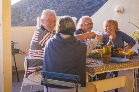 cheerful group of adult couples having fun together cheers with wine eating a grill food in outdor terrace leisure activyt at home. celebrating caucasian people - laughing and funny evening in summer night