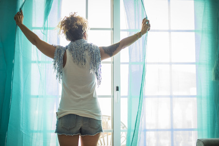 beautiful caucasian woman at home alone opening a window moving the tents. brigh sunny light from outside. daily lifestyle and morning concept. blue tones Archivio Fotografico