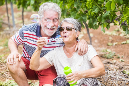 beautiful caucasian mature couple man and woman do soap bubbles together to play and have fun with joy, outdoor nature location for happy leisure activity for retired people with lifestyle