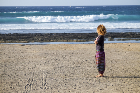 beautiful lonely caucasian middle age woman walk and enjoy the nobody beach in season. freedom and alternative lifestyle concept for independence lady feeling the ocean and nature Stok Fotoğraf - 107344692