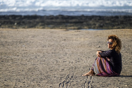 beautiful lonely caucasian middle age woman walk and enjoy the nobody beach in season. freedom and alternative lifestyle concept for independence lady feeling the ocean and nature Stok Fotoğraf