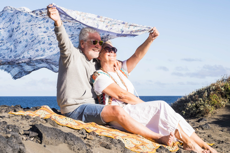senior couple in love forever together have joy stay hugged on the ocean coast in tenerife. enjoyng vacation with freedom and hippy style clothes. nice lifestyle for aged people Foto de archivo