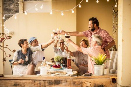 groupe d'adultes âgés de 40 à 80 ans célèbrent ensemble à la maison sur la terrasse avec mets et vins. Amitié ensemble les gens concept s'amuser et beau style de vie souriant beaucoup et vivre heureux en riant Banque d'images