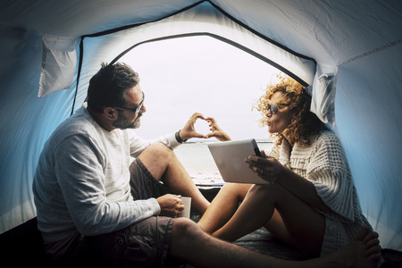 caucasian couple in love inside a tent on a free camping at the beach to enjoy and have fun in a different kind of vacation with adventure and discover.