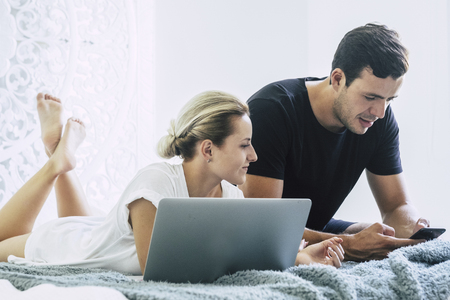 beautiful caucasian couple laying on the bed at home in the bedroom working and using technology notebook laptop and mobile phone. Foto de archivo