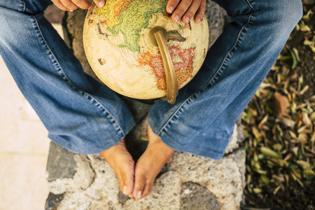 traveler caucasian legs and hands with a earth globe sphere in the middle choosing the next trip journey vacation destination rounding the map.