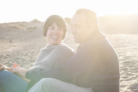 nice beautiful middle age 40 years old couple man and woman caucasian hugged and stay together on the beach sitting in the sand and enjoying a golden amazing sunset for nice leisure activity outdoor in the nature