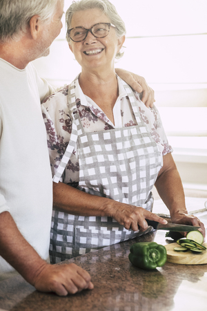 cheerful senior adult couple at home working together in the kitchen cutting fresh seasonal vegetables ready to cook for a healhty lunch. natural and correct lifestyle for mature people Banco de Imagens