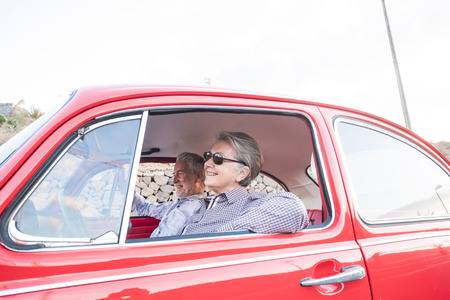 nice adult senior caucasian couple have fun and love inside a red old vintage car parked on the road. smiles and enjoy traveling together. happiness and lifestyle for nice people. summer time and vacation journey